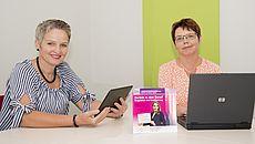 Zwei Frauen sitzen mit Tablet und Laptop an einem Tisch