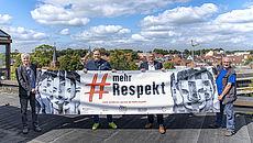 Vier Personen halten ein Banner auf dem Dach des Auricher Kreishauses. Im Hintergrund die Dächer der Auricher Innenstadt.