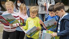 Kinder schauen in das Naturbuch des Landkreises Aurich