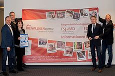 Mitarbeiter der Freiwilligenagentur, KVHS und Harm-Uwe Weber vor dem Plakat der Freiwilligenagentur