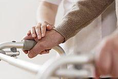 Symbolhaftes Bild einer Pflegekraft mit einer pflegebedürftigen Person
