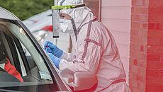Person in Schutzanzug testet andere Person in Auto