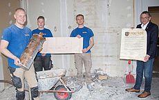 Mitarbeiter der Baufirma und Landrat Olaf Meinen mit der Zeitkapsel