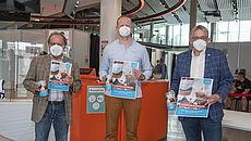 Gerd Bartinger (UNICEF), Impfzentrumsleiter Norman Büchter und Landrat Olaf Meinen bei der Übergabe der Spendenboxen
