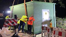 Verteiler-Gebäude hängt an einem Kran und wird zur geplanten Stelle gehoben.