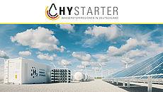 Stockfoto Symbolbild Wasserstofftanks mit Windkraftanlagen im Hintergrund. Leicht bewölkter Himmel.