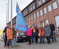 Gruppenfoto vor der Fahne zum Tag gegen Gewalt an Frauen