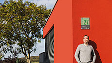 Mann vor rotem Haus mit Grüner Hausnummer