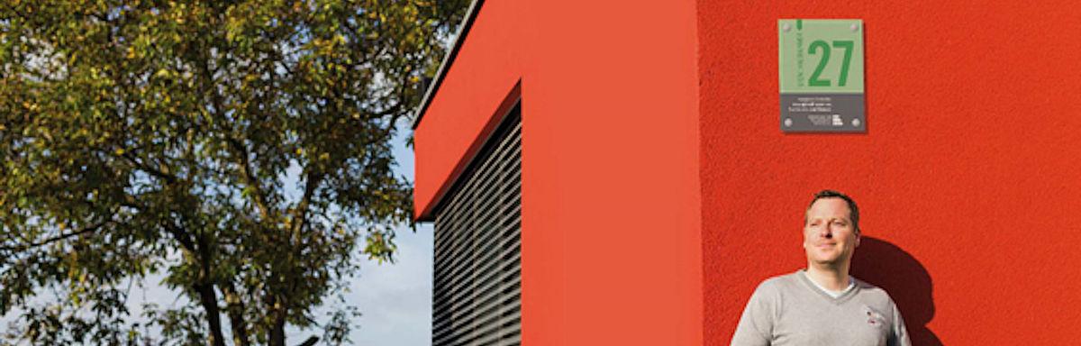 Mann lehnt an rotem Haus mit grüner Hausnummer